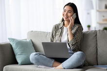 Pretty Young Woman Having Phone Conversation, Using Laptop