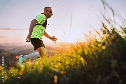Fototapeta Middle-aged mountain trail runner man dressed bright t-shirt with a backpack in sports sunglasses endurance running uphill by picturesque hills at sunset time
