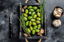 Fresh Green Olives In Wooden Tray With Thyme. Black Background. Top View