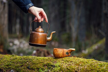 A Man Pours Delicious Coffee From Vintage Teapot Into Wooden Cup On Mossy Old Tree. Forest Background Blurred.