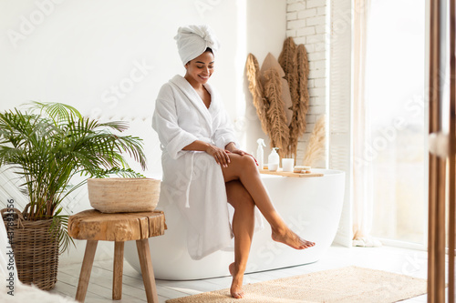 Stampa su Tela African Female Touching Smooth Legs After Depilation Sitting In Bathroom
