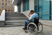 Upset Handicapped Black Man In Wheelchair In Front Of Stairs Without Ramp, Having No Possibility To Enter Building