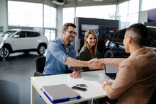 Male Customer And Female Car Dealer Shaking Hands At Showroom.