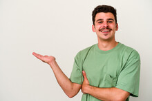 Young Caucasian Man Isolated On White Background Showing A Copy Space On A Palm And Holding Another Hand On Waist.