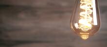 Closeup Of Vintage Modern Light Bulb Over Wooden Background.