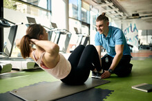 Happy Male Coach Assisting Sportswoman In Exercising Sit-ups In A Gym.