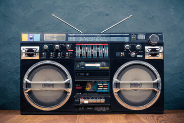 Retro boombox ghetto blaster outdated portable black radio receiver with cassette recorder from 80s front concrete wall background. Rap, Hip Hop, R&B music concept. Vintage old style filtered photo
