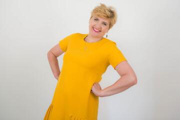 Ładna, elegancka kobieta w średnim wieku w żółtej sukience.