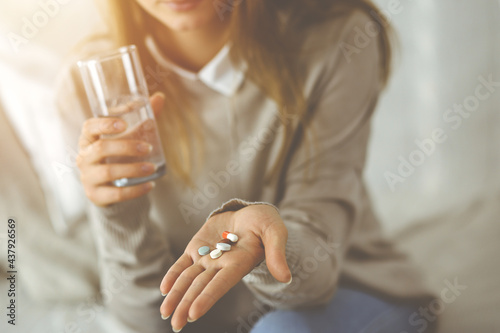 Billede på lærred Close-up woman holding pills time to take medications, cure for headache