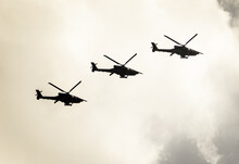 Three Helicopters In Flight. Military Helicopters. Cloudy Sky In The Background.