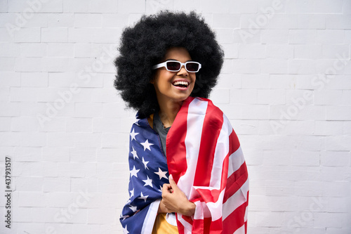 Tablou Canvas Happy smiling African American teenager wearing sunglasses wrapped in usa flag celebrating july 4th forth independence day of united states