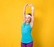 Gym Woman Stretching Arms Up, Doing Gymnastics, Low View Angle, Isolated On Yellow Background. Half Length Of Sportswoman Ready For Exercising. Athletic Female Person. 80s Styling