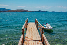 Beautiful Landscape - Summer Resort - Sea Bay With Turquoise Clear Water, Wooden Pier And White Jet Ski, Blue Sky And Mountains On The Horizon. Saranda, Albania.