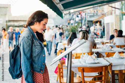 Young tourist woman choosing a restaurant with terrace for dinner Fototapet