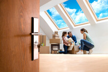 Home, People, Moving And Real Estate Concept - Happy Modern Family Moving Into New House And Unpacking Boxes Together.