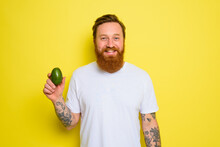 Happy Man With Beard And Tattoos Holds An Avocado