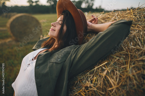 Canvastavla Beautiful stylish woman in hat relaxing on haystack in summer evening field