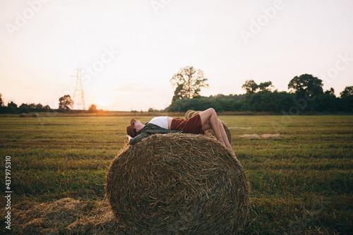 Fotografie, Tablou Beautiful carefree woman in hat lying on haystack in sunset light enjoying evening in summer field