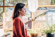 Profile Of Woman Meditating With Eyes Closed On Sunlight Filled Porch