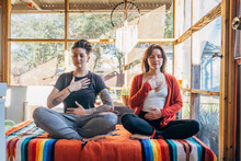 Women Sitting And Meditating Together With Hands On Heart And Stomach