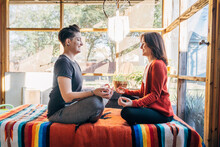 Women Sitting And Meditating Facing Each Other And Laughing