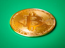 Individual Bitcoin Crypto Currency With Chroma Key Green Screen Background. A Battle Rages Which Is A Better Store Of Value, Digital Versus Fiat Losing Purchasing Power.