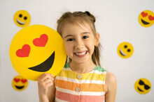 World Emoji Day. Anthropomorphic Smile Face.  Birthday Party. Emotions. A Little Girl, Smiling With All Her Teeth, Holds A Cardboard Love Emoji In Her Hands.