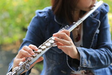Flute Classical Instrument Player Playing Song. Instructor Practicing Bronze Woodwind For Orchestra As Solo With Green Bokeh Outside With Nature.