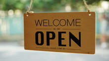 Open And Closed Sign In Front Of Coffee Shop And Restaurant Glass Door. Wooden Sign With Wording Of Place's Status. Say Sorry We're Closed And Another Side Is Welcom We're Open.