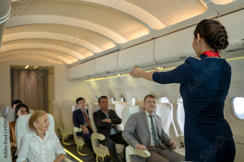 Canvas Print Cabin crew or air hostess demonstrate safety procedures to passengers prior to flight take off in cabin airplane