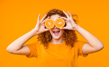 Portrait Of Afro Red Hair Happy Woman Holding Halves Of Orange Near Face