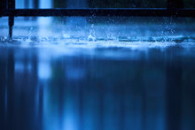 A Blue Scene Of Wet Reflection Floor From Heavy Raining With Splashing Water From Rain Droplet, Photograph Shot With Very Shallow Depth Of Field Focusing