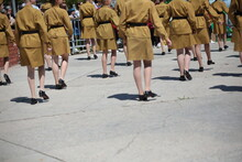 Young Slender Girls In Military Uniforms In A Tunic With A Belt And A Short Khaki Skirt In Black Shoes Are Marching On The Parade Ground.Photography Of A Musical Dance Group At The Festival Russia