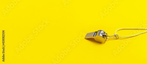 Fotografia Sports whistle on yellow background