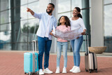 Happy black family traveling with kid, holding map