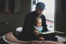 Father Reading Book For Baby Son