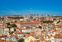 An Airplane Fly Over Lisbon, The Capital City Of Portugal