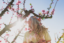 Woman Smelling Blooming Flowers Of Tree