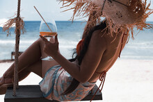 Happy Asian Woman In Bikini Relaxing On Swing With Cocktail. Vacation Concept.