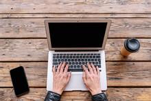 Crop Freelancer Typing On Laptop Between Smartphone And Takeaway Coffee