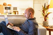 Elderly Man In Earphones Browsing Laptop On Sofa