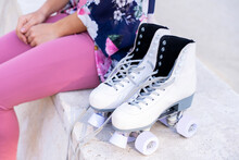 Crop Woman With Modern Roller Skates Resting On Street