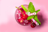 Cold and refreshing summer drink. Cherry cola, limeade, mojito lemonade cocktail with lime and cherries on colorful bright pink background