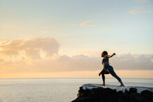 Woman Performing Extended Side Angle Pose Against Sea At Sunset