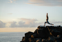 Unrecognizable Woman Performing Crescent Lunge Pose Against Sea At Sunset