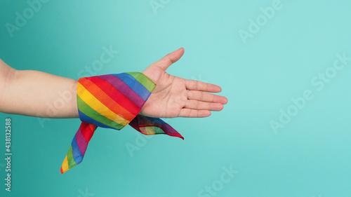 Fotografia Hand with rainbow handkerchief do handshake gesture on mint background or tiffany blue background
