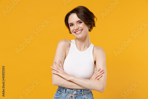 Cuadros en Lienzo Young smiling happy friendly caucasian woman 20s with bob haircut wearing white tank top shirt hold hands crossed folded isolated on yellow color background studio portrait