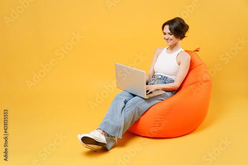 Fotografia Young smiling woman 20s with bob haircut wearing white tank top shirt using lapt
