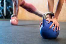 Anonymous Fit Sportswomen Performing Plank Pose With Kettlebells In Gymnasium