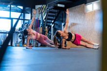 Athletes Performing Side Plank Pose While Practicing Fitness In Gym